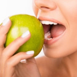 Closeup photo of a beautiful healthy girl biting an apple